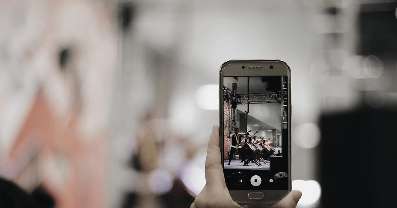 Un móvil fotografiando a un grupo de músicos