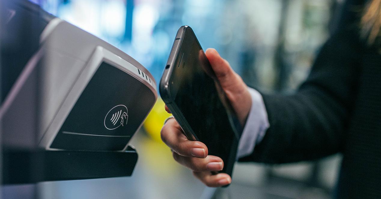 Una mujer haciendo un pago desde el móvil con el sistema NFC