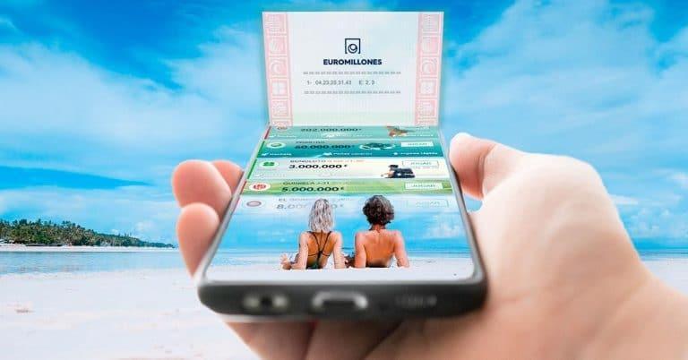 movil en la mano en la playa con app tulotero